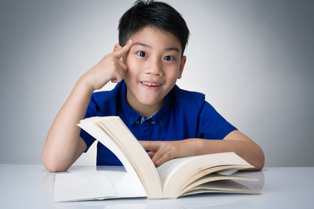 Little asian boy read a book and think on gray background
