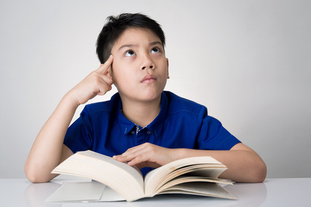 to think about: Little asian boy read a book and think about that on gray background Stock Photo