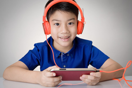 Asian boy ware headphone and playing the cell phone on gray background Stock Photo