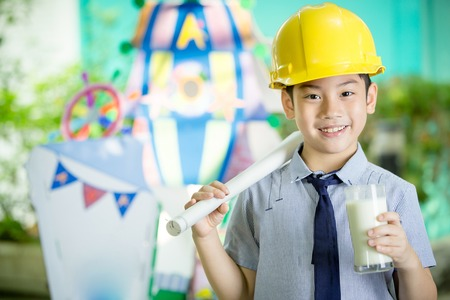Young asian child construction engineer holding a glass of milk