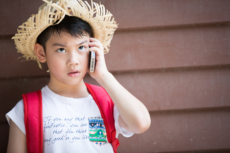 speaks: Asian boy with red backpack speaks by phone