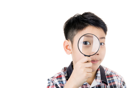 portrait of a young asian child looking through a magnifying glass on white background Stock Photo