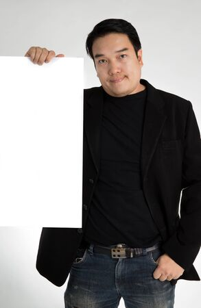 Asian man in black suit holds an empty plate , on a gray background Stock Photo