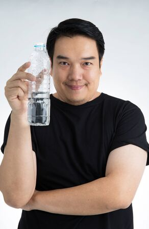 Asian Man in profile drinking fresh water.over on gray background