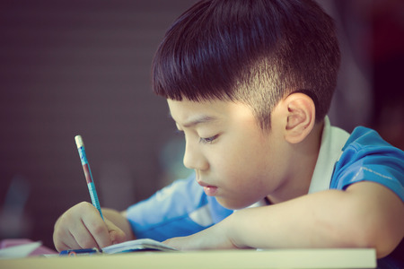 Young asian boy doing his homework, Vintage style Banque d'images