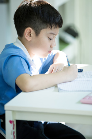 Young asian boy doing his homework