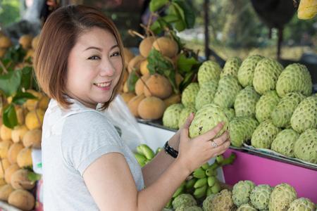 custard apple fruit: Happy asian woman choosing fresh custard apple fruit in the grocery shop on the foreground