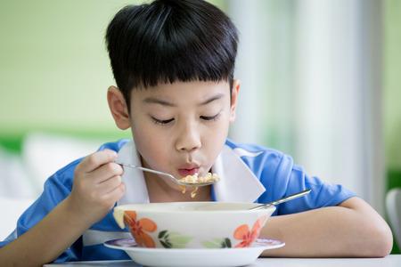 Jonge Aziatische jongenszitting die thuis maaltijd eet Stockfoto