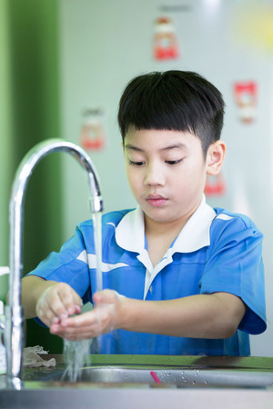 boy room: Little asian boy washing his hands in the kitchen room Stock Photo