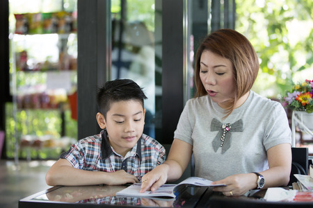 asia smile: Asian Mother reading a book with her son with smile face in living room Stock Photo