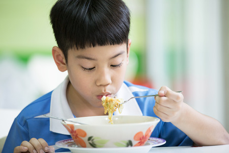 Young asian boy sitting at home eating meal