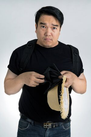 pay cuts: Disappointed Asian traveler on gray background Stock Photo