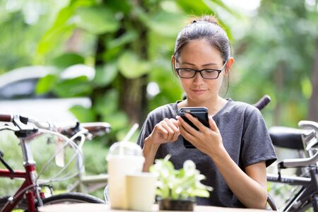 woman with phone: Young Asian woman  using smartphone in garden, looking on screen. Stock Photo