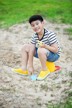 playing with spoon: Asian cute boy playing with toys in garden Stock Photo