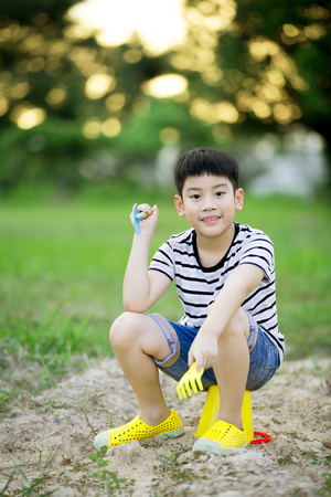 plastic toys: Asian cute boy playing with plastic toys in garden