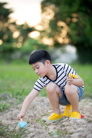 beautiful little boys: Happy Asian cute boy playing with toys in garden