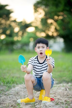 playing with spoon: Happy Asian cute boy playing with toys in garden
