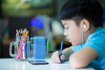 deberes: Un niño usa el teléfono celular y la pintura sobre un papel blanco en casa
