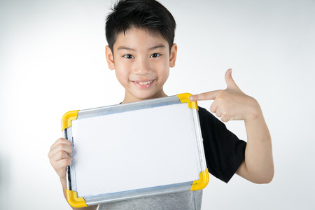students fun: Asian boy is little smile with blank white board and looking camera on gray background
