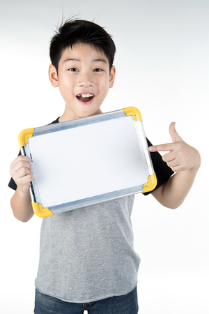 Asian boy is little smile with blank white board and looking camera on gray background