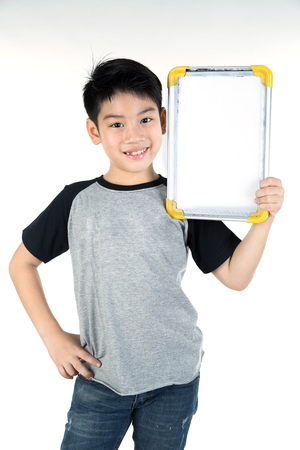 Asian boy is little smile with blank white board and looking camera on white background Banque d'images