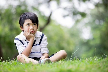 7 year old boys: Portrait of a little asian boy is thinking in the park