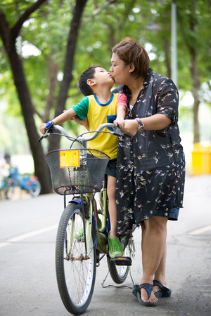 kiss love: Asian Son on bicycle is kissing his mother in the park Stock Photo