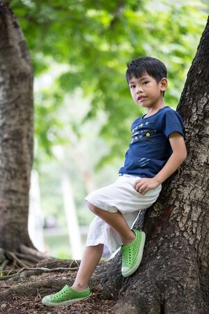 ni�os jugando: portrait of young asian boy stand near tree at the park