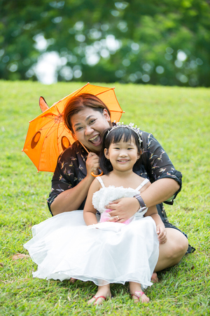 Little asian girl playing on green grass with her mother in the park Stock Photo