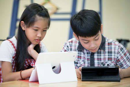 laying little: Little Asian boy and girl are playing together with a computer tablet