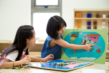 Little asian girl looking at South east asia for play jigsaw on a geographical map