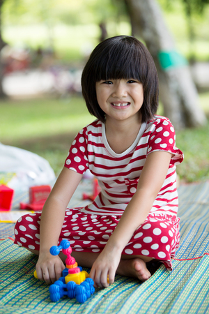 thai stretch: Portrait of asian girl in the park sitting on green plastic mat with toy