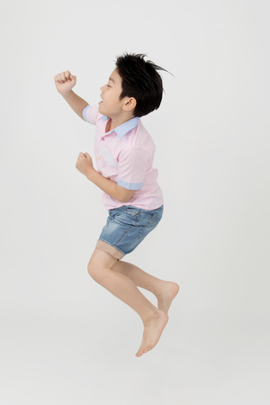 Happy asian boy is jumping at studio on gray background Banco de Imagens
