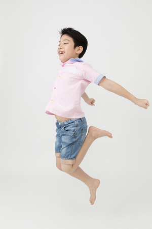 Happy asian boy is jumping at studio on gray background, Stock Photo