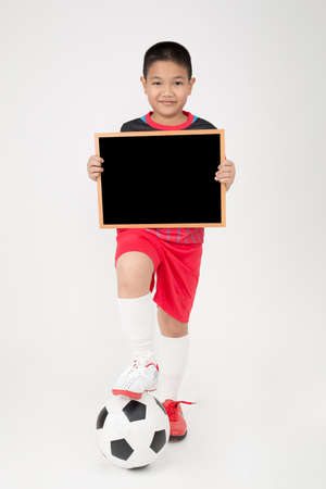 unifrom: Little asian boy holding empty wood blackboard in sports unifrom on gray background Stock Photo