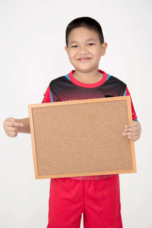 unifrom: Little asian boy holding empty wood board in sport unifrom on gray background Stock Photo