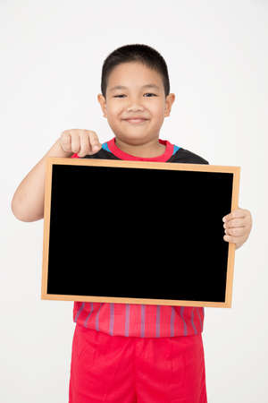 unifrom: Little asian boy holding empty wood blackboard in sport unifrom on gray background Stock Photo