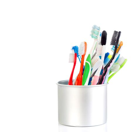 dental health: Group of old and used toothbrush in metal cup isolate on white background