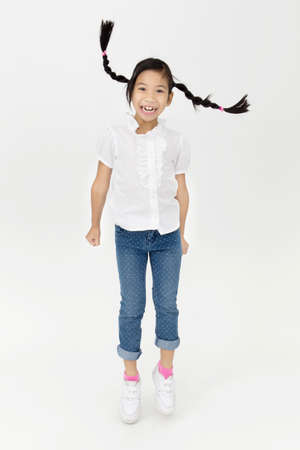 carita feliz: Retrato de la muchacha asi�tica linda est� saltando con cara de sonrisa sobre fondo gris Foto de archivo