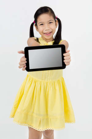 isolated on gray: Little asian girl smiles with tablet computer on isolated  gray background