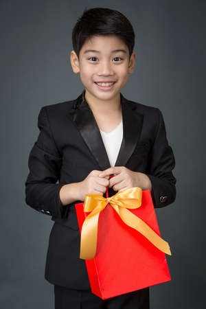 birthday suit: Portrait of asian boy in black suit holding gift bagon gray background