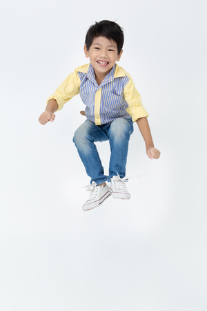 Portrait of asian cute boy is jumping on gray background
