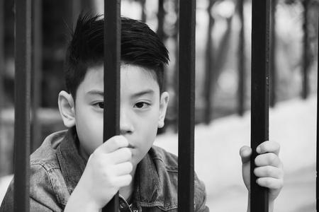 rejas de hierro: El muchacho asiático tras las rejas de hierro, Negro y tono blanco
