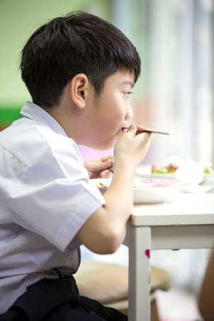 Asian boy is eating by him self at home Stock Photo