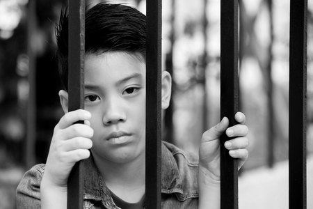 incarcerated: asian boy behind iron bars ,Black and white tone