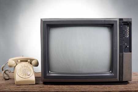 vintage television: Vintage Television with old telephone on wood table on gray background