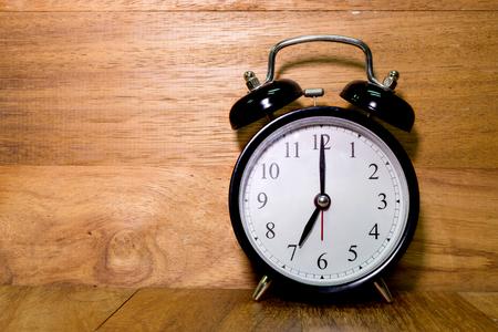 seven o'clock: Vintage background with retro alarm clock on wood background, Alarm clock shows Seven o`clock