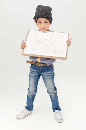 asian art: Happy Asian little artist boy holding a blank art board  on gray background