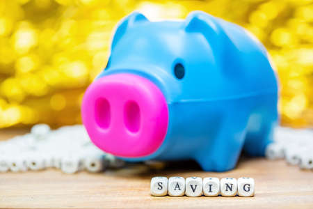 Blue piggy bank with Saving message on white bokeh background