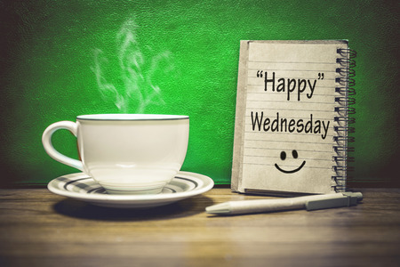 Inspirational quote - Happy  Wednesday, on notepad, retro style background. Focus Text message on notepad area .